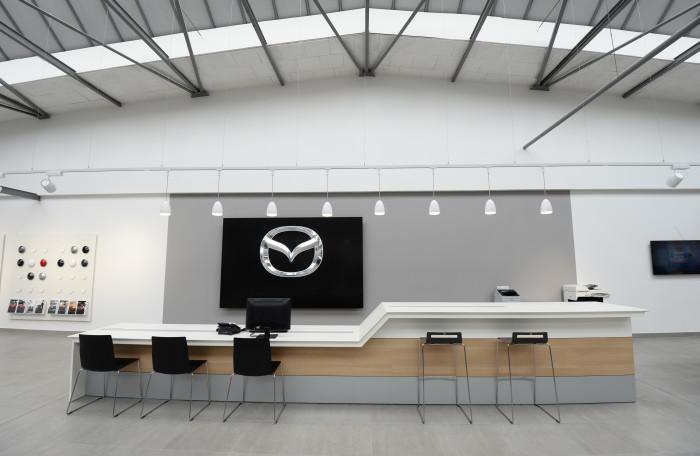 Wirkt wie ein Fremdkörper: das auf schwarzem Display befindliche Markenzeichen hinter dem Tresen. Quelle: Mazda